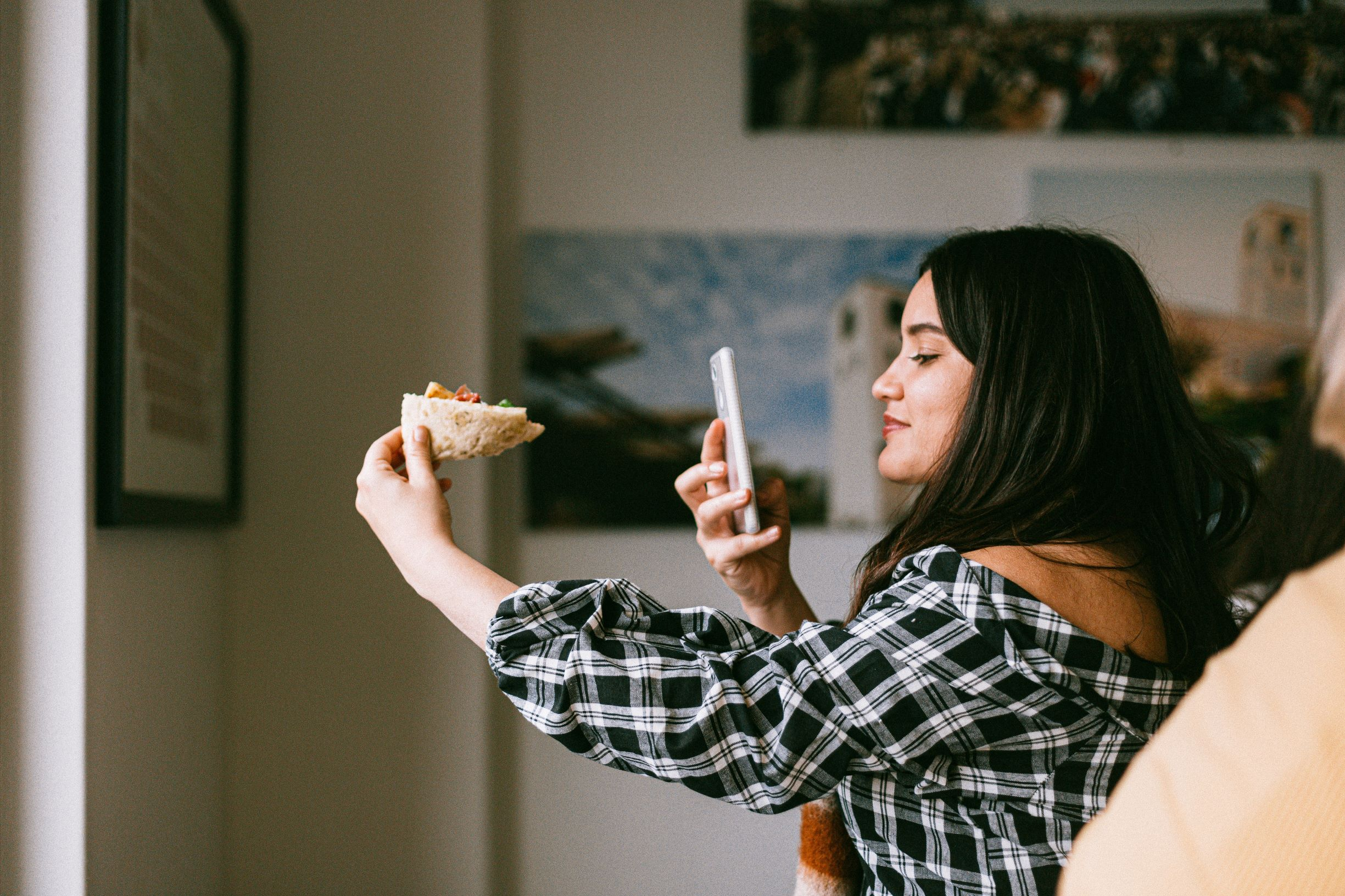woman taking a photo of pizzza