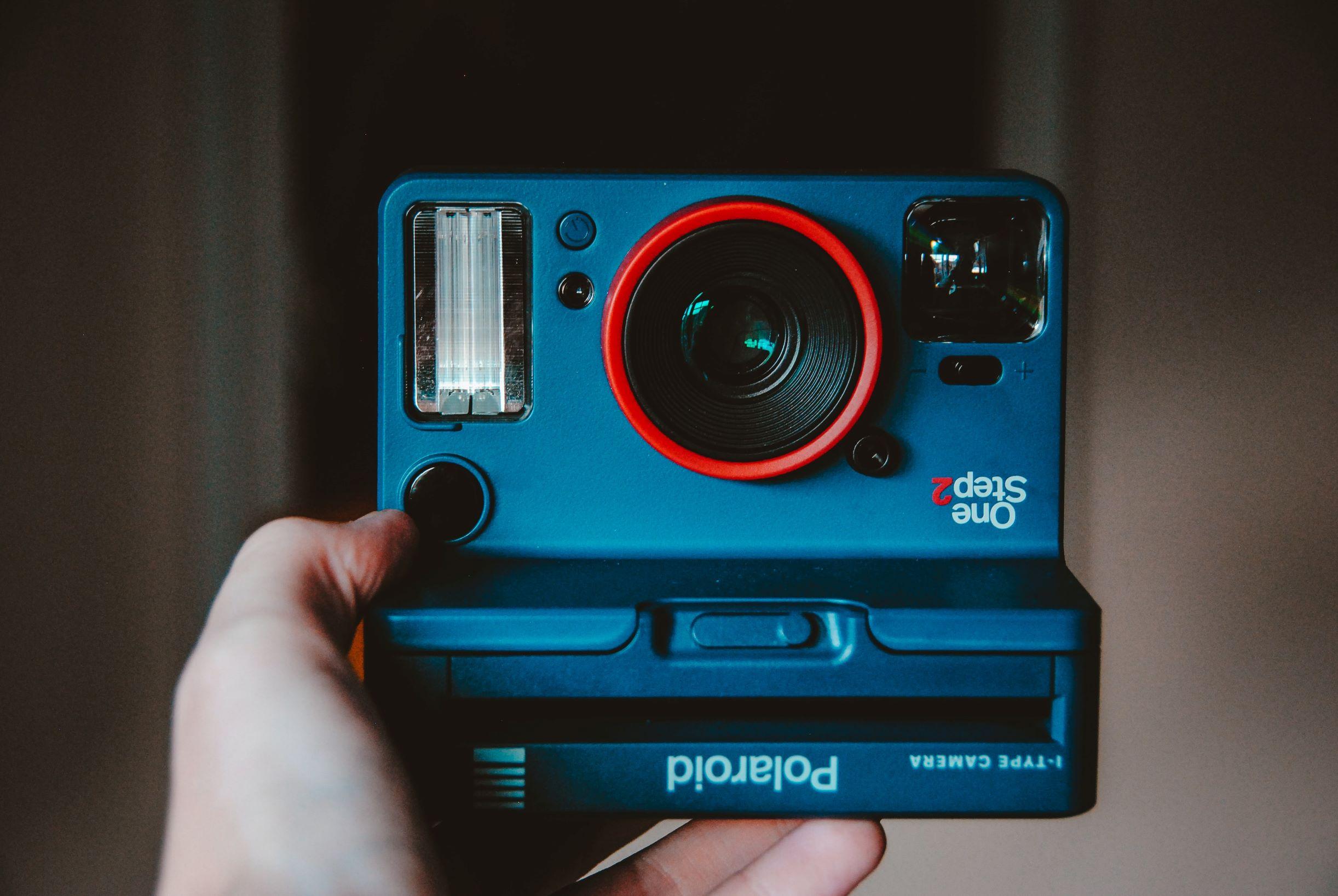 a hand holding a polaroid camera