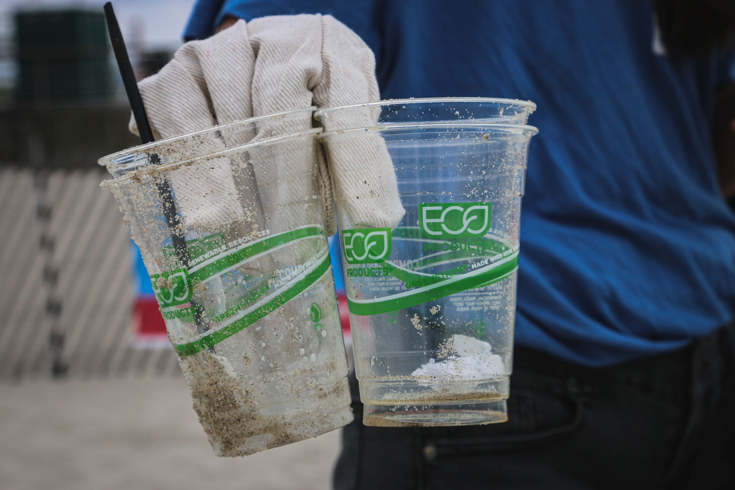a hand in golves holding 2 plastic cups covered with sand